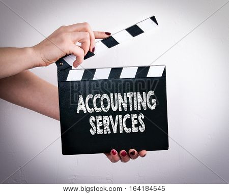 Accounting Services. Female hands holding movie clapper.
