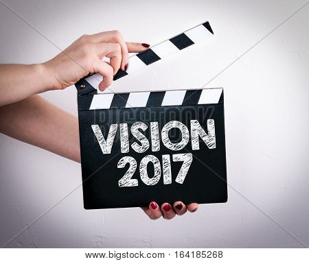 Vision 2017. Female hands holding movie clapper.