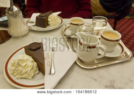 VIENNA, AUSTRIA - JANUARY 2 2016: The original Sacher Torte served with whipped cream and coffes at Hotel Sacher Hotel in Vienna