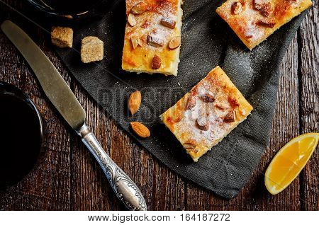 Lemon Ricotta cake with almonds sprinkling on wood background.