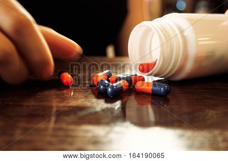 Orange-blue pills spilled out of bottle on polished wooden table and girls hand holding one of it.