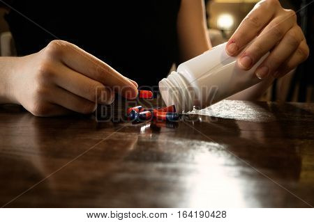 Woman gets out pills from white plastic bottle on polished table and takes one by hand.