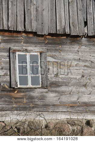 The wall of an old wooden house with on window