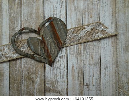 A rusty heart crafted from corrugated metal, a lacy burlap ribbon, and boards with peeling paint create a rustic approach to love and friendship.  Copy space.