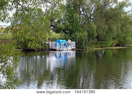 TARKHANI RUSSIA - AUGUST 28 2016: Boat with a canopy from the sun for swimming on the pond in the Lermontov estate Tarkhani