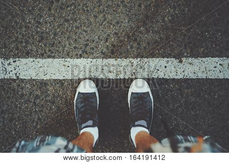 View of feet of man in white socks and gumshoes standing near grunge white line on gray asphalted road ready to pass