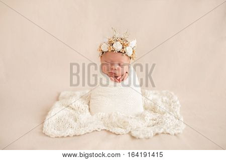 Newborn Baby In A White Cocoon.baby With An Ornament On His Head, With Cute Ears And Flowers.
