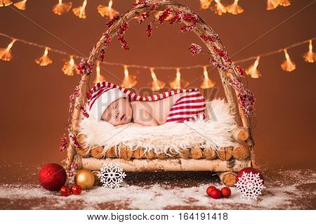 Newborn Baby Sleeping In A Wooden Crib. The Striped Suit Elf On A Brown Background.