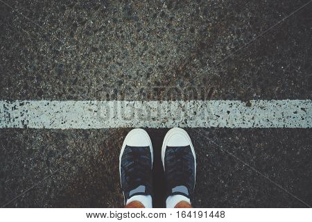 Male feet in white socks and gumshoes standing near grunge white line on gray asphalted road ready to go