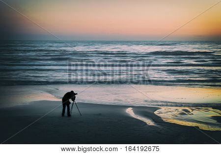 Silhouette of the photographer on the seashore