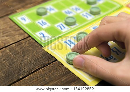 Old lotto game cards on wood background