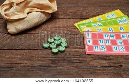 Old lotto game pieces and cards on wood background