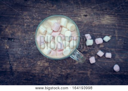 Marshmallows on the top of a hot chocolate drink in a glass on wooden background. Fluffy hot chocolate cappuccino coffee in a cup with marshmallow. Christmas drink. Top view.