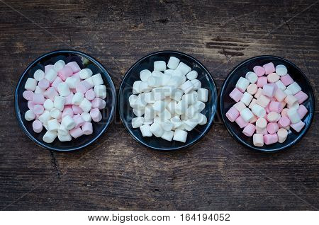 Colorful mini marshmallows in a black plates on a wooden background. Different mini white pink and orange puffy marshmallows. Marshmallow concept. Top view.