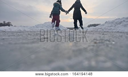 People skate on skating rink in the winter on ice, active winter sports holiday family