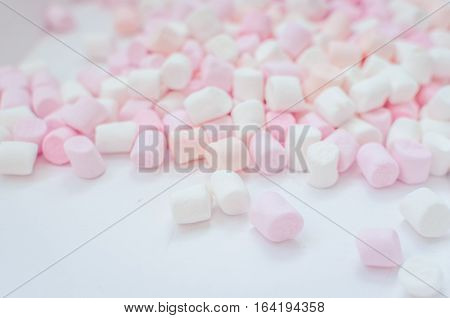 Colorful mini marshmallows background close-up texture. A pile of different mini white pink and orange puffy marshmallows. Marshmallow concept. Wallpaper for desktop. Selective focus.