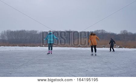 People sports skate on skating rink in the winter on ice, a active winter holiday family