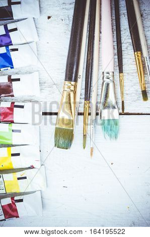 Artist paint brushes and oil paint tubes on white wooden background. Brush paint artistic. Tools for creative work. Watercolor paintbox. Back to school. Paintings Art Concept. Top view. Copy space.