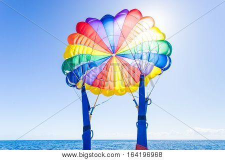 Looking up towards a colourful parachute into the sun