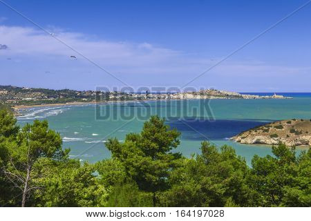 Summertime relax.The most beautiful coasts of Italy: bay of Vieste.-(Apulia, Gargano) -In the foreground the Gattarella islet and in the background Castello or Scialara beach and the town of Vieste.