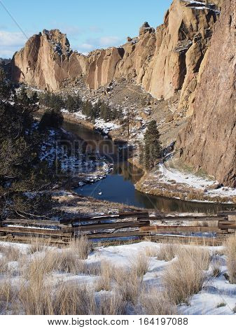 The Crooked River winding through the canyon at Smith Rocks State Park in Central Oregon with fresh snow a fence wild grasses and towering geological formations on a winter day.
