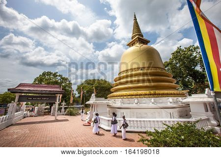 DAMBULLA, SRI LANKA. July 22, 2016: Golden Temple Peace Pagoda Stupa in Dambulla, Sri Lanka. Some women in traditional Sri Lankan dress walking near the temple.