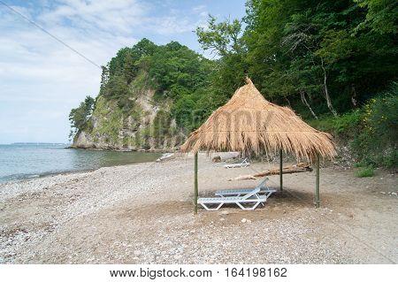View of deckchairs on white pebble sea beach