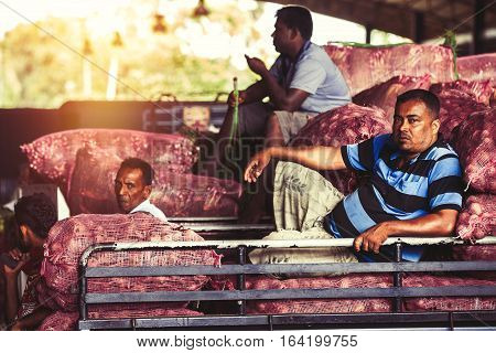 DAMBULLA, SRI LANKA. July 23, 2016: Workers in a vegetable market in Dambulla Sri Lanka are resting after a lot of hard work. Truck loaded with vegetables.