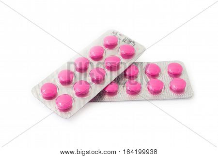 Pink pills in blister pack on white background