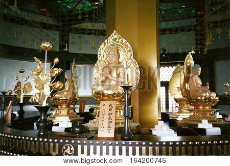 NARITA, CHIBA / JAPAN - CIRCA NOVEMBER, 1987: Buddhist images sit on an altar, inside the Narita-san Shinshō-ji Shingon Buddhist temple in Narita, Japan