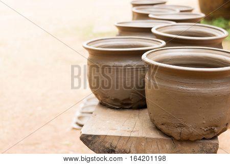 drying new handmade earthenware on wooden shelf
