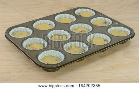 Raw orange cranberry muffins in paper muffin cups in muffin baking pan