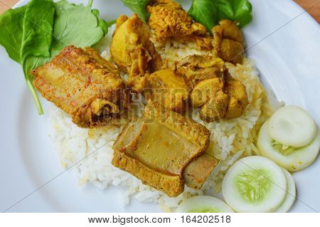 pork rib and chicken in yellow curry on plain rice