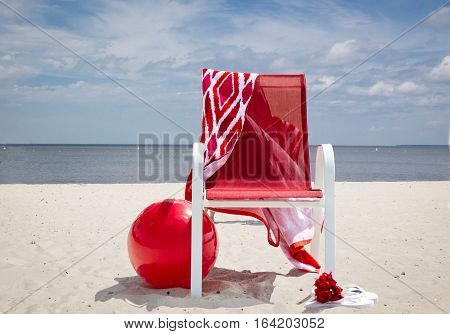 horizontal image of a red beach chair with a red and white towel hanging over the back and a big red beach ball lying on the sandy beach with the lake in the background in the summer time.