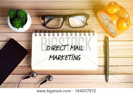 Top view of earphone, smartphone, plant, eye glasses, alarm clock, pen and open notebook written with DIRECT MAIL MARKETING on wooden background.