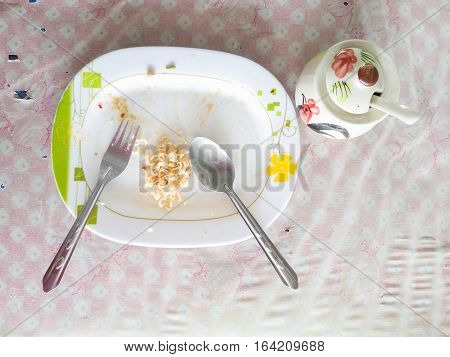 Plate of spaghetti noodle at the end of a meal on a table