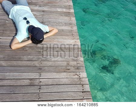 Man lying on the dock pier wooden bridge with a hat and sun glass over summer sea beach. Summer vacation relaxation