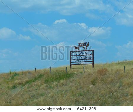 Sign:  BEEF It's what's for dinner.  Has a cow on top with a big check mark, long fence roll, big sky, clouds, and funny.  Shot in Laramie County while on vacation.