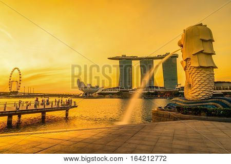 SINGAPORE-JULY 9 2016: Merlion statue fountain in Merlion Park and Singapore city skyline at sunrise on July 9 2016. Merlion fountain is one of the most famous tourist attraction in Singapore.