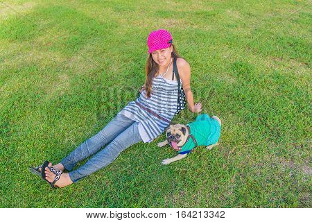 Portrait of a asian teenage woman girl sit rest with her cute dog puppy pug outdoors on fields