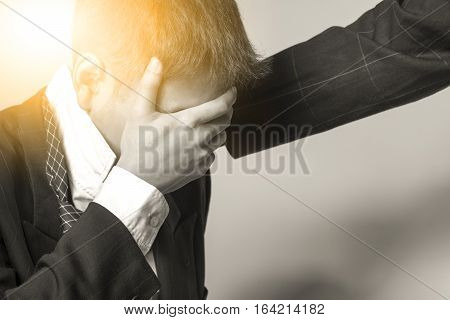 Businessman taking his hand on face himself feeling sad and failure  in business financial and another businessman give a moral support black and white color under the sunlight