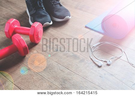 Fitness concept with sneakers red dumbbells yoga mat and earphones on wood floor Copy space