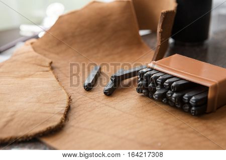 tools for homemade leathercraft on brown background