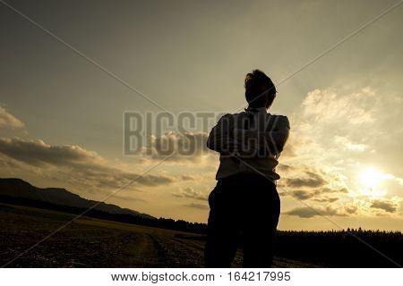 Silhouette of a man at sunset standing with folded arms and his back to the glowing sun low angle with copy space.