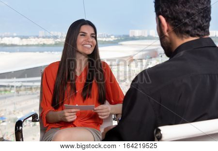 Beautiful latin female presenter asking a famous celebrity at tv studio