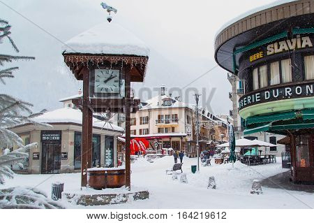Chamonix, France - January 30, 2015: Street view with clock, cafe and central square in Chamonix, one of the oldest ski resorts in French Alps