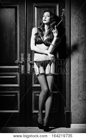 Film noir style: sexy beautiful young woman in lingerie standing at the door and smoking cigarette. Black and white
