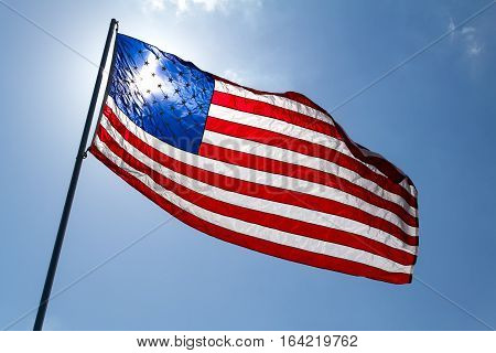 American flag with sunlight shining through it.