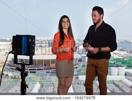 Beautiful latin female presenter and caucasian man at tv studio