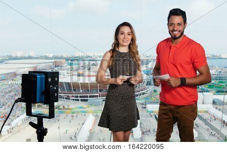 Beautiful caucasian female presenter and latin man at tv studio